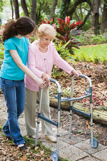 Caregiver offering senior citizen mobility assistance